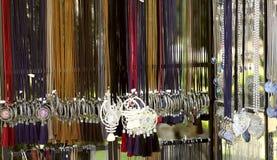 垂悬的妇女的首饰的图象在色的鞋带的在商店 在脖子的时兴的首饰妇女的 库存照片