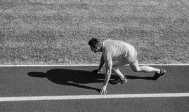 初学者的跑的技巧 人运动员立场低开始状态体育场道路 准备好的赛跑者去 联合流动性 免版税库存照片