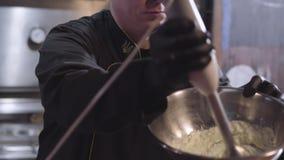 制服和黑橡胶厨师手套的厨师鞭打与搅拌器的sause在大铝碗关闭 食物准备 股票录像