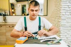 制服的电工检查芯片,杂物工 库存图片
