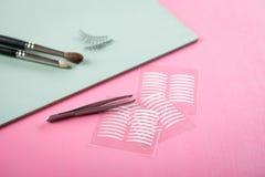 刷子、假鞭子、镊子和人为眼皮折痕双重磁带眼睛构成的在淡色淡粉红色和薄荷的绿色 库存图片
