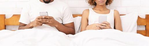 分别地在床上的千福年的夫妇与智能手机 库存照片