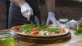 切与路辗刀子的厨师厨师比萨在木桌上在比萨店 削减在切片的pizzaillo的关闭热的比萨 影视素材