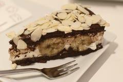 切片与奶油、巧克力和杏仁的香蕉蛋糕在上面,在有叉子的一块板材服务 在可口蛋糕的选择聚焦 库存图片