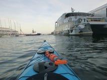 划皮船在游艇附近 库存照片