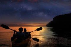 划皮船在有百万星星系的海洋的剪影母亲和女儿 库存图片