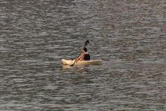 划皮船的完美的日子 用浆划美丽的年轻女人,当坐在皮船时 库存图片