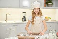 Ładna dziewczyna w szefów kuchni kapeluszowych kulinarnych ciastkach na kuchni fotografia stock