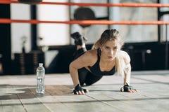 Ładna kobieta patrzeje kamerę ups od drewnianej podłogi w gym podczas gdy robić pcha fotografia royalty free