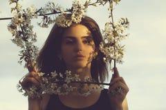 Ładna kobieta pozuje w kwiecistej ramie na niebieskim niebie zdjęcie royalty free