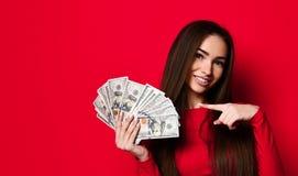 Ładna kobieta trzyma wiązkę pieniędzy banknoty w czerwieni sukni obrazy stock