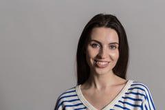 Ładna kobieta z puszystym włosy, ubierającym niezobowiązująco przeciw szarej studio ścianie fotografia stock