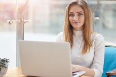 Ładny żeński uczeń z ślicznym uśmiechem przygotowywa dla testa w kawiarni Piękna szczęśliwa kobieta pracuje na laptopie podczas k obraz stock