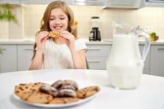 Ładny dziewczyny obsiadanie przy stołem, łasowań ciastka z rodzynkami fotografia royalty free