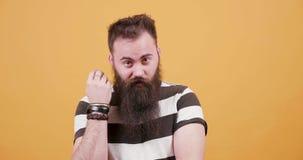 Ładny młody brodaty mężczyzna ubierał w koszulce przed żółtym tłem zbiory
