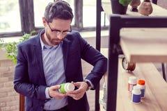 Ładny poważny mężczyzna czyta inskrypcję na butelce zdjęcia stock