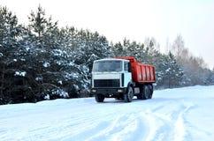 Ładunku usypu ciężarówka jedzie na śnieżnej drodze ładować piasek w karierę Zimy droga przeciw tłu bajecznie świerkowi drzewa obraz stock