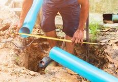Łamana drymba w dziury i wody ruchu przy pobocze hydraulika działania naprawą z Pomiarową taśmą obraz stock