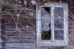 Łamany okno w zaniechanym drewnianym domu przeciw jako tła popasu pojęcia dolarom szarość wiesza haczyka fotografia stock