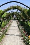 Łukowaty droga przemian wykładający z kwiatami obrazy stock