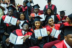 哥罗德诺,白俄罗斯- 2018年6月:方形的学术毕业盖帽和黑雨衣的外国非洲医科学生在期间 免版税库存照片