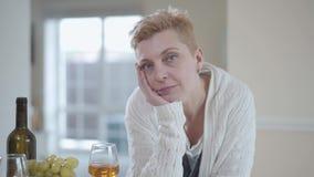哀伤的资深妇女画象在桌倾斜的白色毛线衣的看在照相机户内紧密  背景是 股票录像