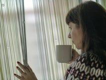 冬天毛线衣的美女,看通过窗帘窗口,拿着一杯咖啡 免版税库存图片