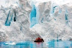 冰川产犊在南极州,黄道带的人们在冰川的悬崖前面 库存图片