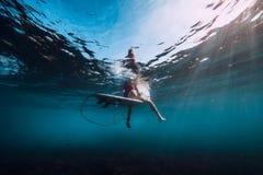 冲浪板水中的年轻海浪女孩在海 库存图片