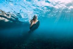 冲浪板水中的年轻海浪女孩在海 库存照片