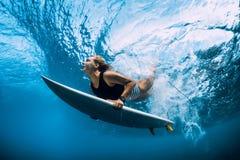 冲浪者在水面下妇女下潜 在波浪下的Surfgirl下潜 免版税库存照片