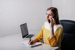 写在笔记薄和打电话,当坐在办公室时的少年女孩 免版税库存照片