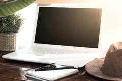 冒险在计算机上的假期计划 与西部帽子,植物,笔记本,铅笔的表 库存图片