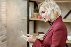 凝视在智能手机屏幕上的严肃的白肤金发的妇女 免版税库存图片