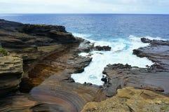 击中夏威夷海岛的岩石海岸蓝色海浪 免版税库存图片