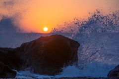 击碎和飞溅在一个热带海滩的岩石的海波浪,在美好的温暖的日落光 库存照片