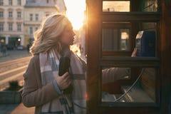准备好年轻美丽的白肤金发的妇女打一次重要电话在葡萄酒公共电话电话亭在一个晴朗的晚上 免版税库存照片