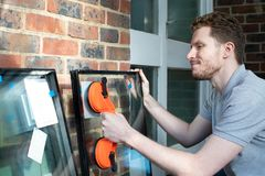 准备的建筑工人适合玻璃入新的Windows 库存照片