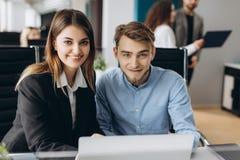 商人和妇女射击工作书桌的看照相机和与计算机一起使用 被聚焦的企业的队  免版税库存照片