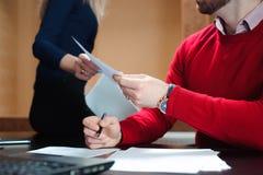 商人的手通过文件的 人们在谈论的办公室举行会议和战略 免版税库存照片