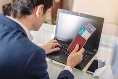 商人藏品在互联网上的机票和护照购买使用膝上型计算机 在网上购买和预定 免版税库存图片
