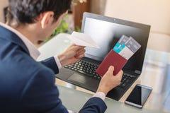 商人藏品在互联网上的机票和护照购买使用膝上型计算机 在网上购买和预定 库存照片