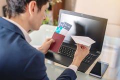 商人藏品在互联网上的机票和护照购买使用膝上型计算机 在网上购买和预定 免版税库存照片