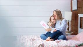 全景愉快的女孩祝贺她的母亲节礼物假日明信片的年轻妈妈 股票录像