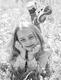 全盛时期概念 微笑的面孔的女孩花费休闲户外 孩子享受春天晴朗的天气,当说谎在草甸时 免版税库存图片