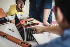 关于遇见建筑图纸的亚洲建筑师商人小组讨论计划 建设工程工具和 免版税图库摄影