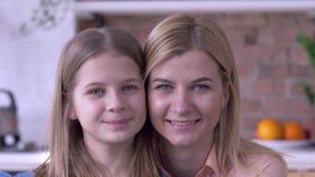 关心的姐妹画象,有蓝眼睛的可爱的小和成人女孩是在家微笑和看照相机