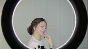 关闭与空气吹的头发的诱人的深色的妇女面孔,看照相机 圆环光秀丽 影视素材