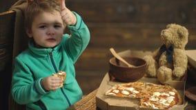 关闭吃薄饼的小逗人喜爱的男孩 男孩吃一可口比萨 在木背景的可口意大利薄饼 股票录像