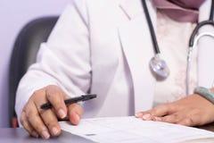 关闭在本文的身体局部女性医生手文字处方食谱与在桌上的笔 库存图片